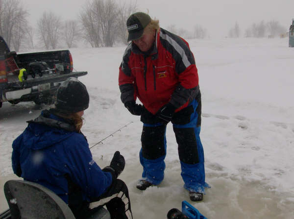 Big Jim McLaughlinshowing Angie some tips on ice fishing.